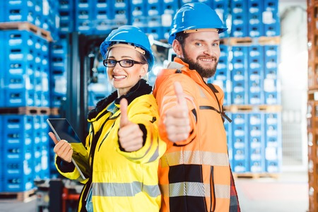 Workers in logistics distribution center showing thumbs-up after having a success