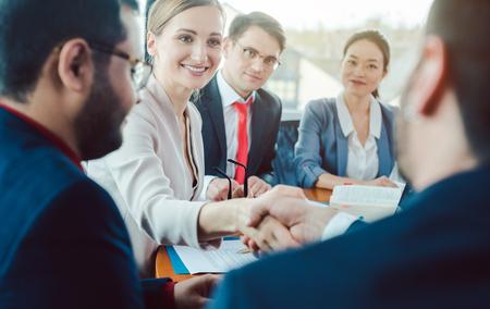 Team von Geschäftsleuten, die eine Vereinbarung aushandeln, die den Deal mit Handschlag abschließt Standard-Bild