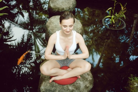 Woman doing yoga at a pond with gold fish sitting on a stone
