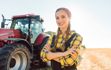 Farmer woman driving a tractor on the field to the harvest