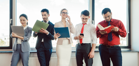 Diversity team of business people working in the office on different tasks Stock Photo