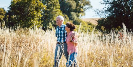 Senior man and woman enjoying themselves and nature having walk over a meadow