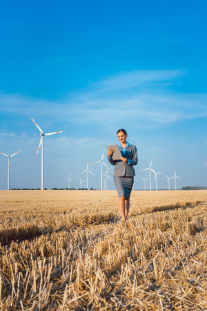 Women putting money into an ethical Investment of wind turbines, standing with her computer on a field