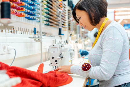 Absorbed seamstress working in her studio sewing clothes 写真素材