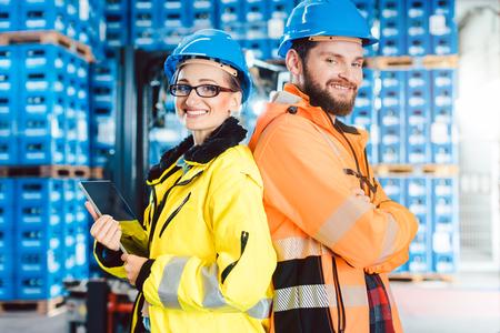 Femme et homme de travailleur dans l'affichage d'entrepôt pour la caméra Banque d'images