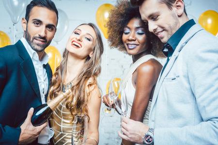 Persone in festa in un club che celebrano e versano champagne nei bicchieri