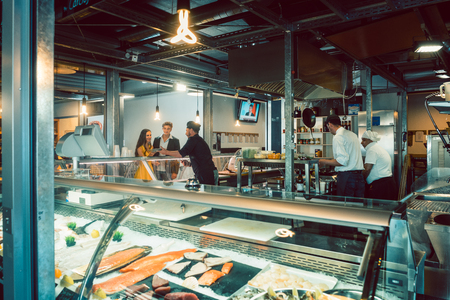 Young couple ordering food at the recommendation of an experienced chef at the counter of a trendy restaurant with fish specialties