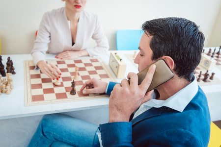 Business people playing chess with man on the phone and woman waiting for him to go on