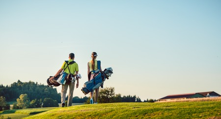 Full length of a happy couple with a healthy lifestyle wearing golf outfits, while carrying stand bags with professional clubs towards the golf course in a sunny day of summer Zdjęcie Seryjne