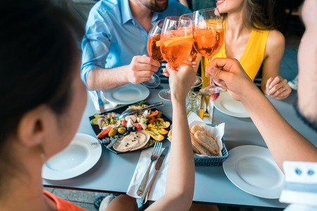 Four friends holding stemmed wine glasses while toasting together with a cold refreshing alcoholic drink during a delicious lunch at the restaurant Фото со стока