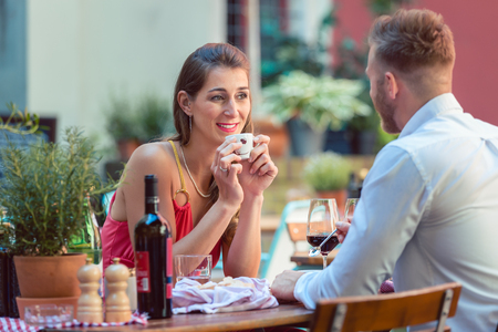 Woman holding cup and looking at her boyfriend in restaurant