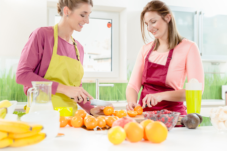Portrait of smiling two young women taling and cutting fresh oranges in kitchen