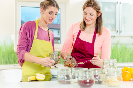 Two woman preparing healthy oatmeal breakfast by adding almonds and chia seeds in the bowl