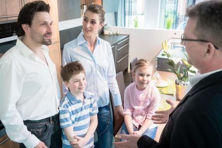 Familia y hombre de ventas en la sala de exposición de la cocina discutiendo Foto de archivo