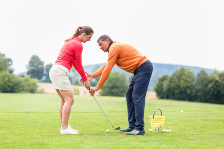 Male golfer giving training to woman for taking a shot on golf course Stock fotó