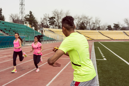 Rear view of a man holding stop watch while two female athletic running on ground 스톡 콘텐츠