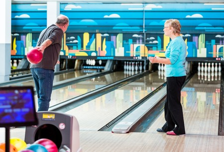 Rear view of a mature man playing bowling game in club Imagens