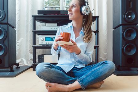 Femme buvant du café et écoutant de la musique assise sur le sol de sa maison