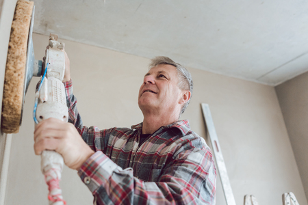 Plasterer smoothing interior wall of new homes with machine