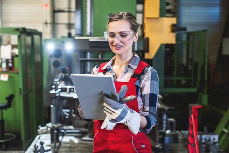 Skilled female worker with tablet computer in front of machine