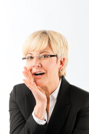 Happy blonde mature businesswoman saying secret against white background