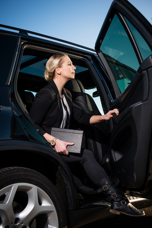 Businesswoman in suit holding diary alighting from car