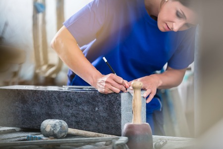Diligent craftswoman applying template for engraving on headstone