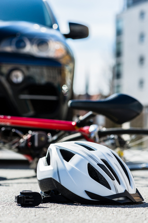 Close-up of a bicycling helmet fallen on the asphalt  next to a bicycle after car accident on the street in the city Stock Photo