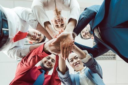 Squadra di diversi uomini d'affari che impilano le mani insieme, visti dal basso