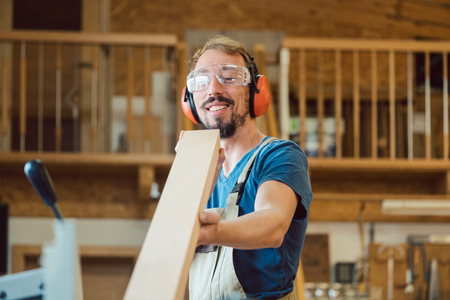 Diligent Carpenter checking his wood work for faults