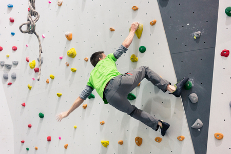 Brave athletic man climbing on wall without protection of rope
