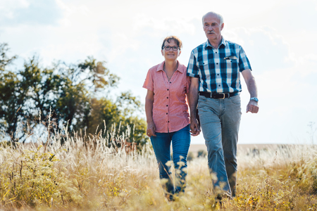 Senior couple walking over meadow holding each others hands still in love Stock Photo