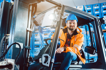 Proud worker in warehouse sitting in his forklift