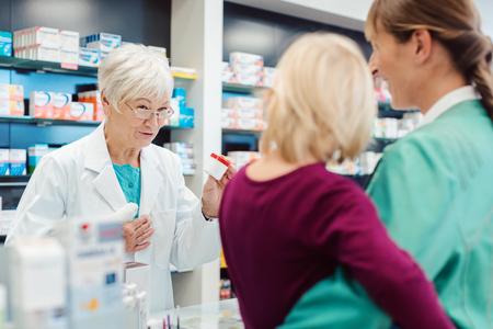 Senior Apotheker im Gespräch mit Mutter mit ihrem Kind erklären die Auswirkungen von verschreibungspflichtigen Medikamenten
