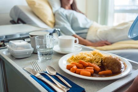 Voedsel afgeleverd bij een patiënt in ziekenhuisbed, focus op de maaltijd