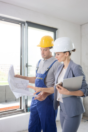 Construction worker and architect looking at plan or blueprint on site Фото со стока