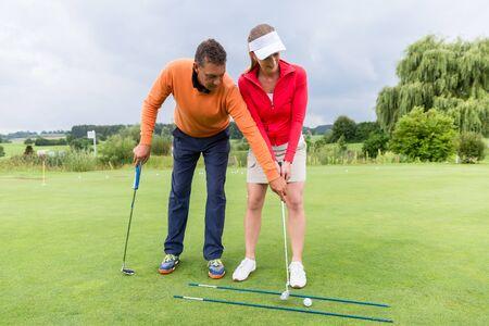 Junge Golfspielerin an der Driving Range mit einem Golftrainer