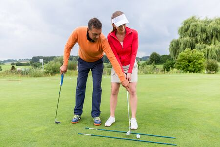 Young female golf player at driving range with a golf coach