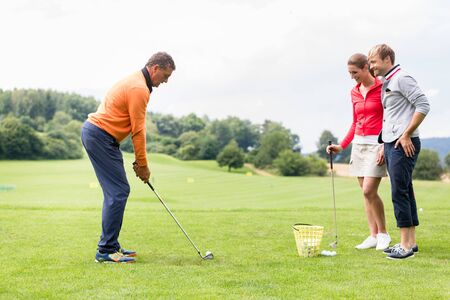 Smiling couple looking at male coacher taking a shot on golf course Stock Photo
