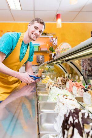 Vendeur de crème glacée dans sa boutique au comptoir avec beaucoup de saveurs au choix