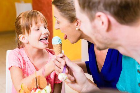 Fille et sa mère léchant un bol de crème glacée ensemble