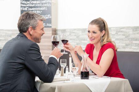 Happy couple toasting glasses of wine in restaurant