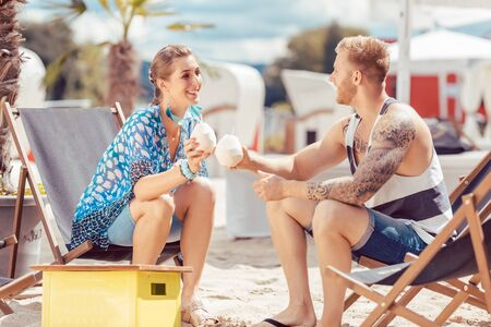 Happy young couple at beach sitting on chair enjoying coconut water