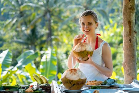 Woman in jungle gazebo sipping on a coconut and eating exotic foods