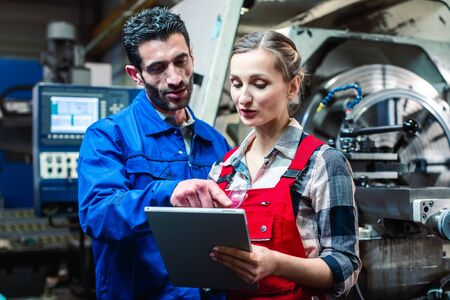 Woman and man manufacturing worker in discussion writing on tablet computer Фото со стока