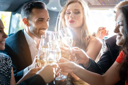 Couple celebrating party in limousine with friends and alcohol Zdjęcie Seryjne