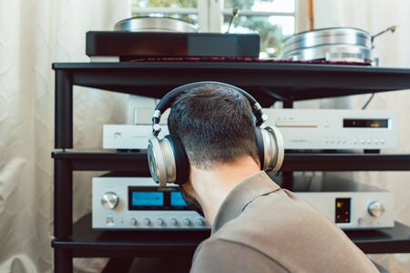 Man turning up the volume on home Hi-Fi stereo for louder music Banque d'images