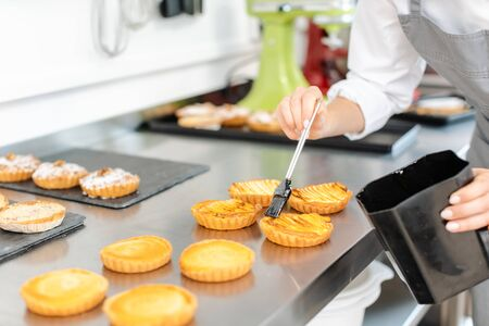 Pastry chef woman glazing little cakes