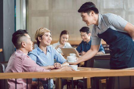 Sonriente joven pareja servida con café en la mesa del café Foto de archivo