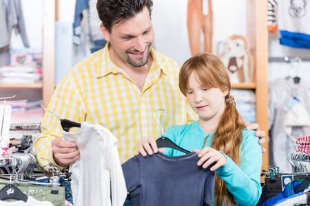 Father looking at daughter choosing t-shirt in the retail shop